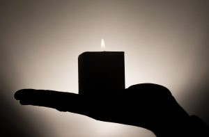 silhouette-of-human-hand-holding-candle-bw